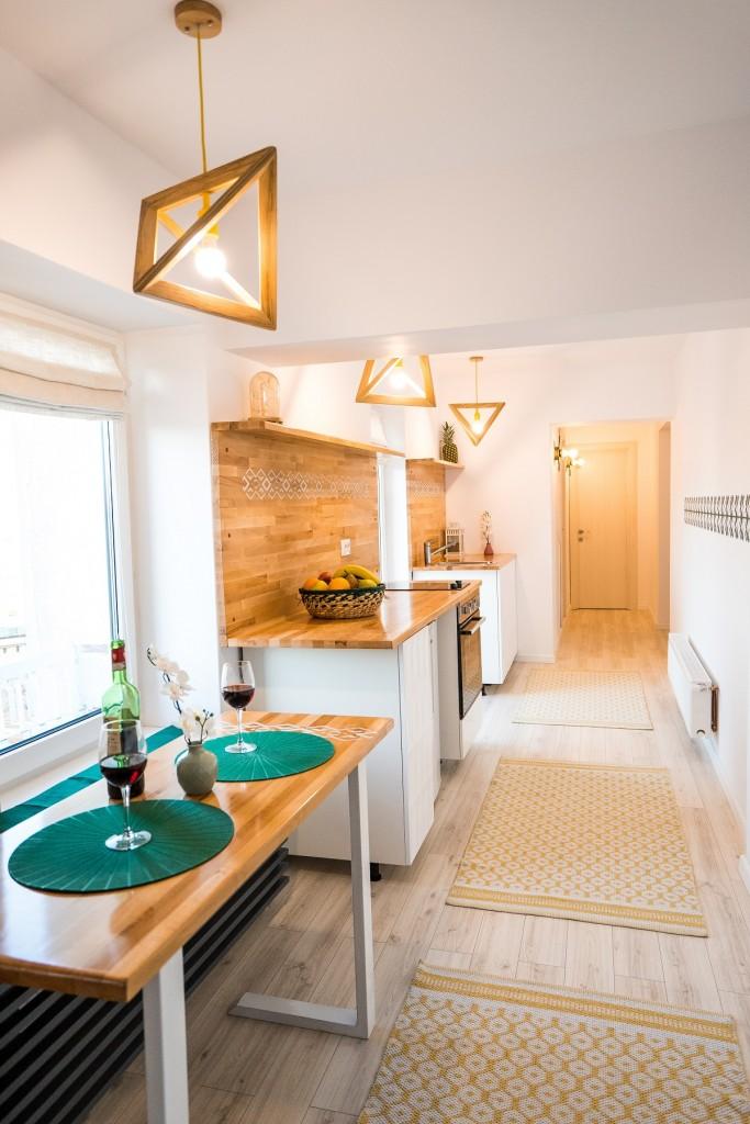 In aceasta bucatarie amenajata de UGinteriors pentru Airbnb, corpurile de iluminat cu lemn se asorteaza cu mobilierul de bucatarie